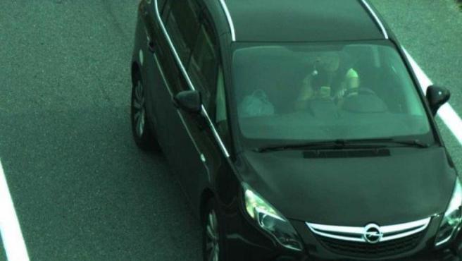 Una mujer mira su teléfono móvil mientras conduce.