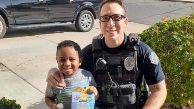 Un agente de policía le lleva un Happy Meal a un niño de 5 años.