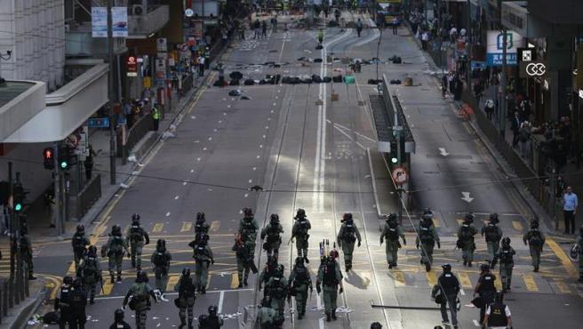 Patrullas policiales recorren el tramo vacío de una avenida de Hong Kong, durante una protesta multitudinaria en una jornada de huelga.