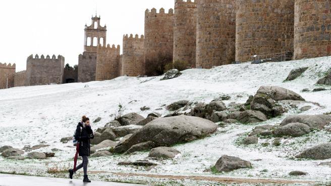 Una mujer camina junto al lienzo norte de la muralla de Ávila .