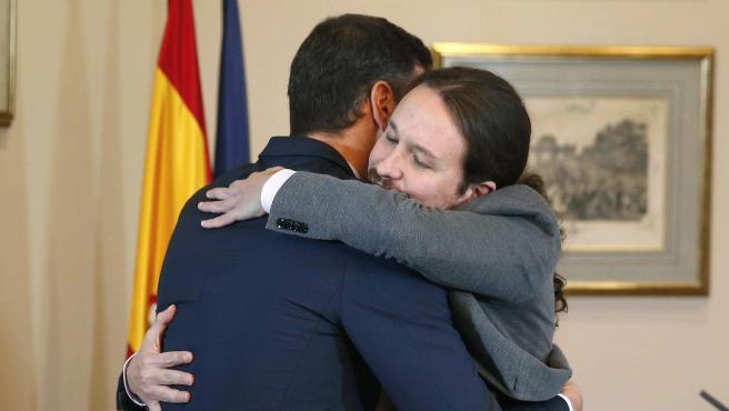 El presidente del Gobierno, Pedro Sánchez, y el líder de Unidas Podemos, Pablo Iglesias, se abrazan en el Congreso de los Diputados tras firmar un acuerdo para la formación de un Gobierno.
