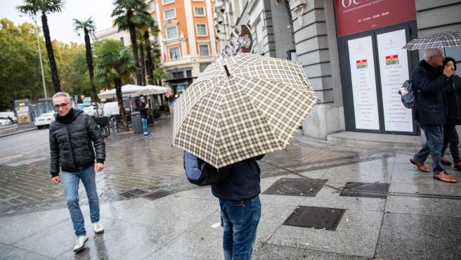 Una persona paseando con un paraguas debido a la lluvia.