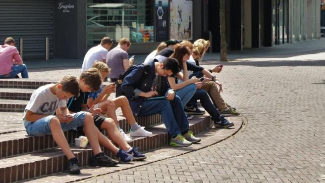 Adolescentes consultando sus teléfonos móviles.