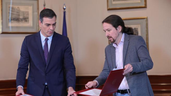 El presidente del Gobierno en funciones, Pedro Sánchez y el líder de Podemos, Pablo Iglesias, se estrechan la mano en el Congreso de los Diputados con el documento del principio de acuerdo para compartir un gobierno de coalición.