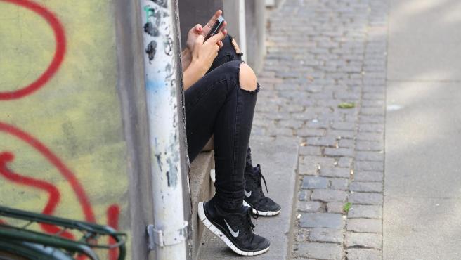 Imagen de archivo de una adolescente con un móvil en la calle.