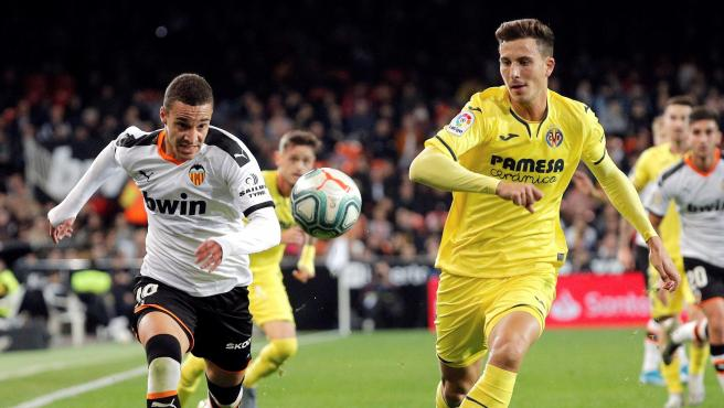 Rodrigo (Valencia) pugna por un balón con Pau Torres (Villarreal).