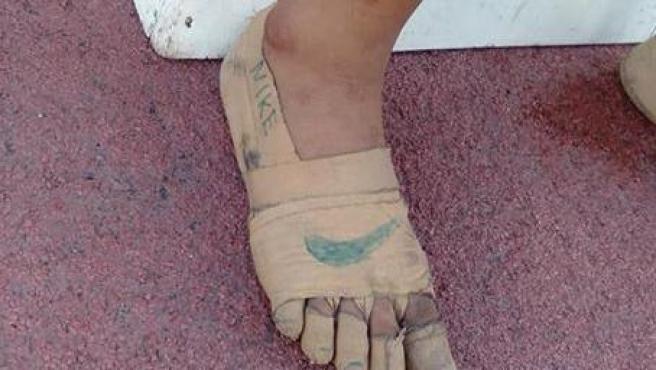 Los pies de la joven atleta filipina, con el logo de Nike pintado en unas vendas.