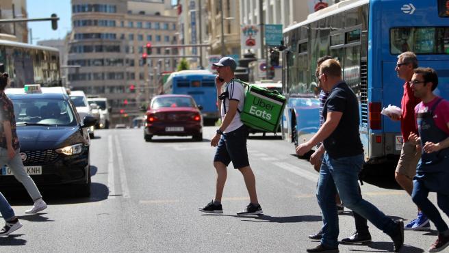 Un 'rider' cruza la Gran Vía de Madrid con la mochila de reparto, en una imagen de archivo.