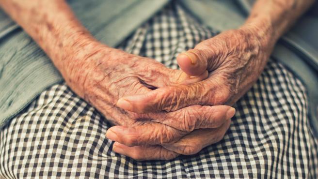 Una anciana con las manos entrelazadas.
