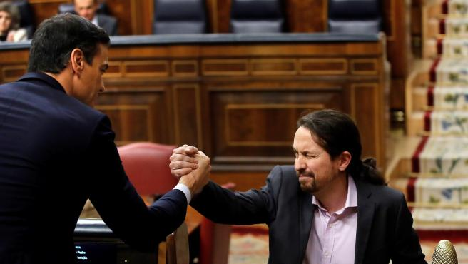 El líder de Unidas Podemos, Pablo Iglesias, saluda a Pedro Sánchez (i), tras su intervención ante el pleno del Congreso de los Diputados en la primera jornada de la sesión de investidura.