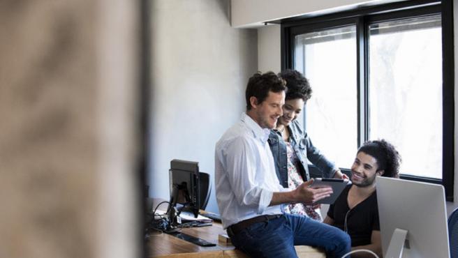 Trabajadores hablando en una oficina. Imagen de archivo.