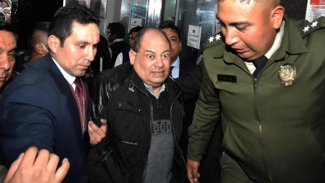 El exministro boliviano Carlos Romero llega a la Fiscalía de La Paz bajo custodia policial para declarar por un caso de supuesta corrupción.