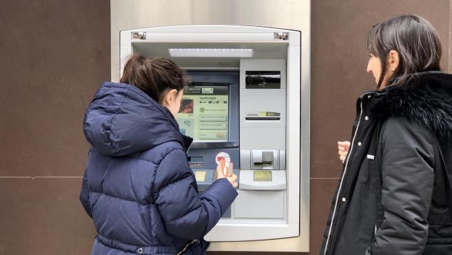 Una madre entrega a su hija una tarjeta bancaria de débito.