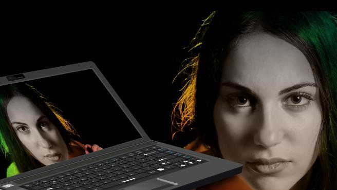 Un ordenador con la cara de una mujer que está al lado de ese mismo ordenador.
