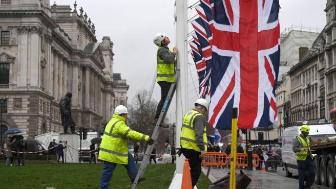 Operarios colocando banderas británicas en la plaza del Parlamento de Londres dentro de los preparativos para la culminación del brexit.