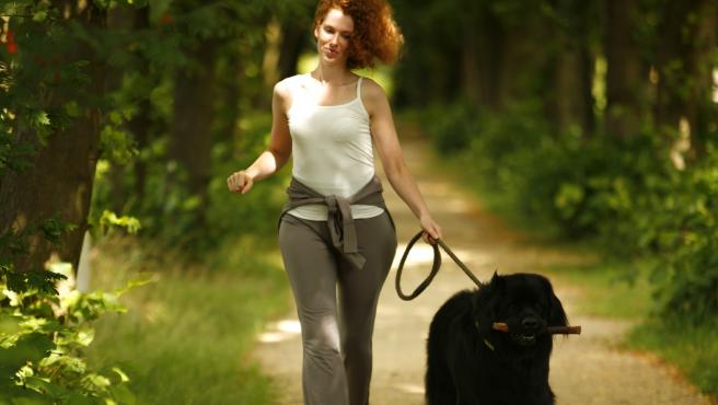 Imagen de una joven paseando a su perro.
