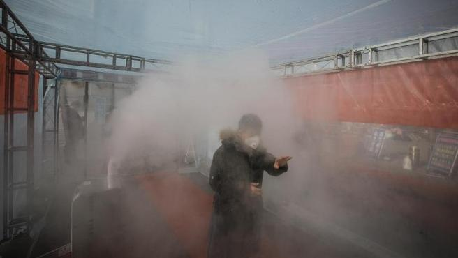 Un hombre es rociado con desinfectante en una instalación temporal habilitada en el municipio de Tianjin, en China.