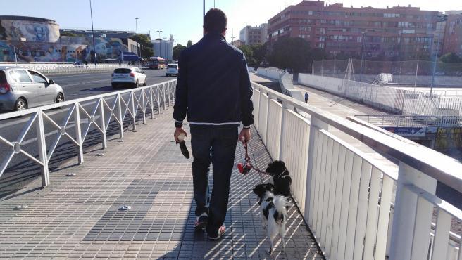 Un dueño de perro pasea por Sevilla con una bolsa para excrementos y una botella de agua.