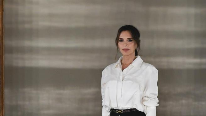 Victoria optó por unos pantalones palazzo largos negros y una camisa blanca abullonada.