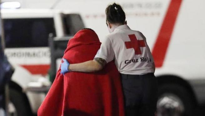 Una voluntaria de Cruz Roja ayuda a uno de los inmigrantes llegados al puerto de Arguineguín (Mogán) a bordo de la 'Salvamar Menkalinan' tras ser rescatados de una patera a 55 kilómetros al sur de Gran Canaria.