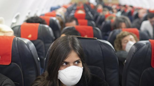 Una pasajera, con una máscara en un vuelo entre Israel e Italia.