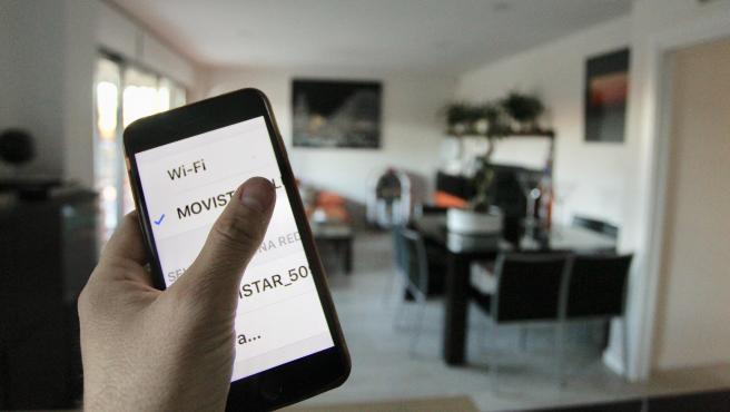 Un usuario conecta su smartphone a la red wifi de su hogar.