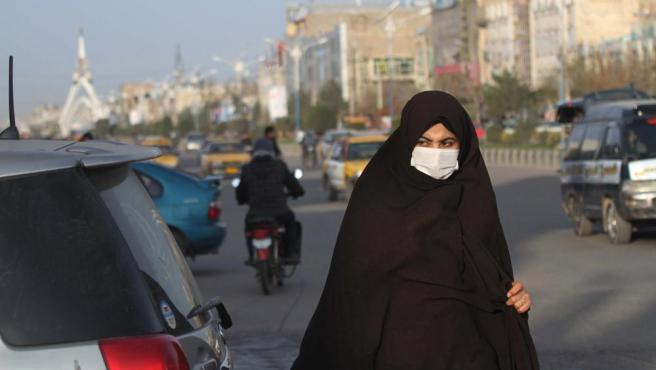 Una mujer lleva una mascarilla de prevención tras confirmarse en Herat el primer afectado del país.