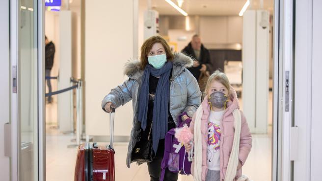 Algunos pasajeros se protegen con mascarillas a la llegada al aeropuerto de Moldavia.