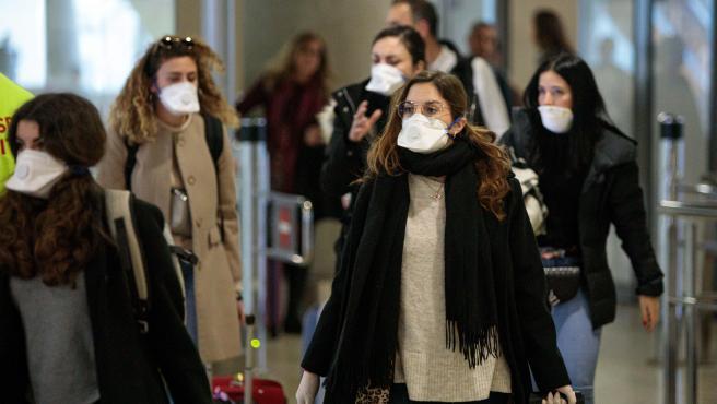 Viajeros procedentes de Italia protegidos con mascarillas a su llegada al aeropuerto de Manises (Valencia).