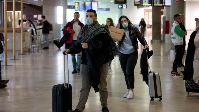 Viajeros procedentes de Italia portan mascarillas a su llegada al aeropuerto de Manises (Valencia).
