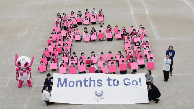 Niños con mascarilla anuncian que quedan seis meses para el inicio de los Juegos.
