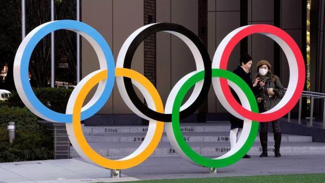 Los Aros Olímpicos, en Tokio, junto a una mujer con mascarilla.