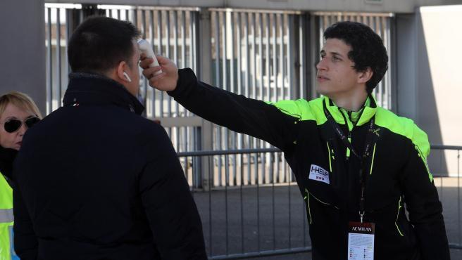 Un trabajador sanitario le toma la temperatura a un periodista a la entrada de un estadio de Milán.