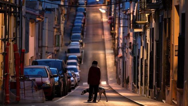 Una mujer pasea a su perro por las calles vacías de Barcelona.