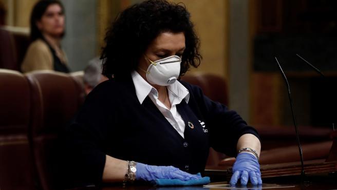 Valentina, una de las empleadas del Congreso, limpia el estrado del hemiciclo tras la intervención de Pedro Sánchez en el pleno extraordinario por el coronavirus.