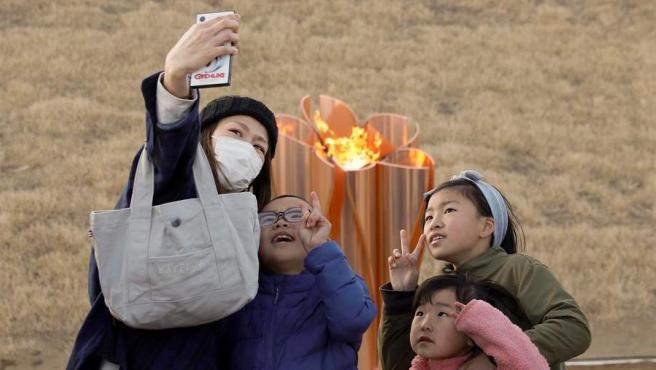 Una familia se hace una foto junto a la antorcha olímpica, expuesta en el parque dedicado a las víctimas del tsunami de 2011, en Ishinomaki, Japón.