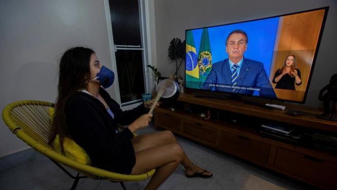 Una mujer con una mascarilla protesta golpeando una olla durante una declaración televisada del presidente de Brasil, Jair Bolsonaro, sobre el coronavirus COVID-19, en Brasilia.