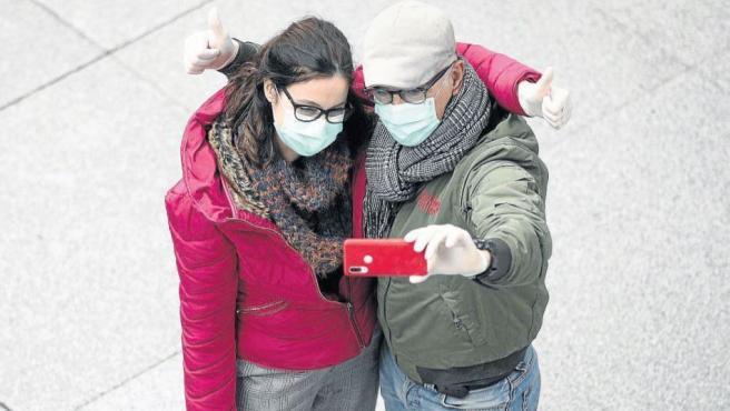 Una pareja se hace un selfi con mascarillas en Madrid.