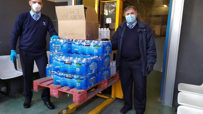 Dos trabajadores voluntarios de la EMT en el reparto de agua y alcohol desinfectante.