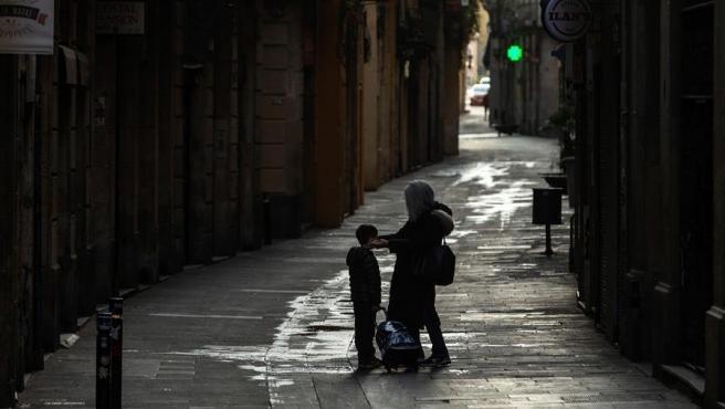 Una madre coloca la máscara a su hijo en una calle del casco antiguo de Barcelona.