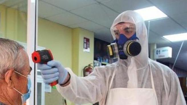Un empleado de un supermercado de Torrevieja controla la temperatura a los clientes antes de entrar.