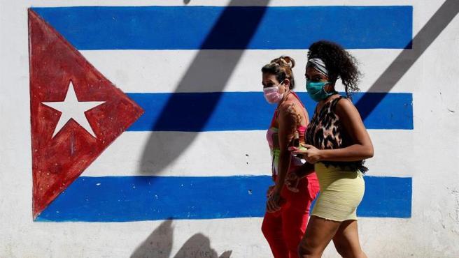 Dos mujeres con mascarillas por el coronavirus COVID-19 caminan frente a un graffiti de la bandera cubana, en La Habana.