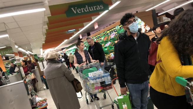 Una persona con mascarilla en un supermercado.