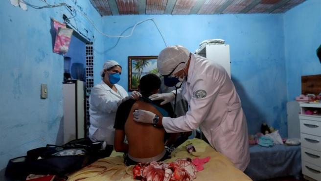 Dos médicos atienden a una persona con síntomas del coronavirus en una zona de favelas de Sao Paulo (Brasil).