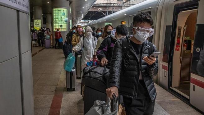 Pasajeros con mascarillas por la pandemia del coronavirus esperan en una estación de Pekín tras llegar desde la ciudad de Wuhan, China, para ser trasladados al lugar donde pasarán una cuarentena.