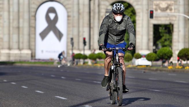 Un ciclista circula cerca de la Puerta de Alcalá, en la que luce un crespón negro por las víctimas de la Covid-19.