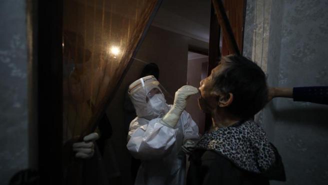 Un trabajador médico realiza un test de COVID-19 a una persona en Wuhan, China.