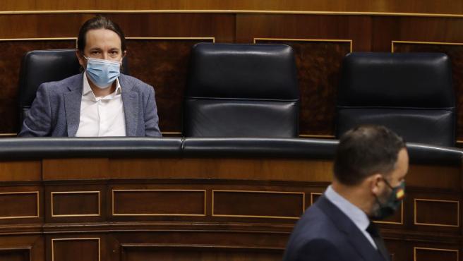 El presidente de Vox, Santiago Abascal, pasa delante del escaño del vicepresidente tercero del Gobierno, Pablo Iglesias, a su llegada al pleno del Congreso.