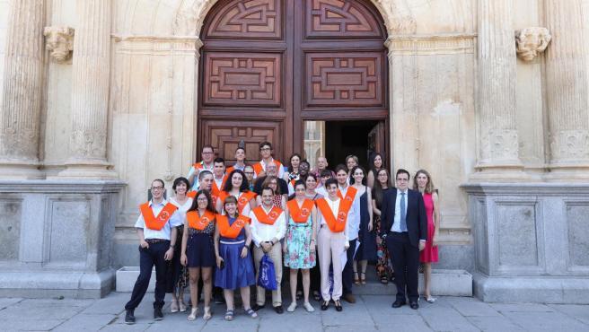 Foto de graduación de jóvenes con discapacidad intelectual ante la fachada de la Universidad de Alcalá de Henares.