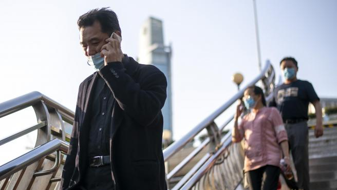Varias personas caminan con mascarilla en Sanghai (China)